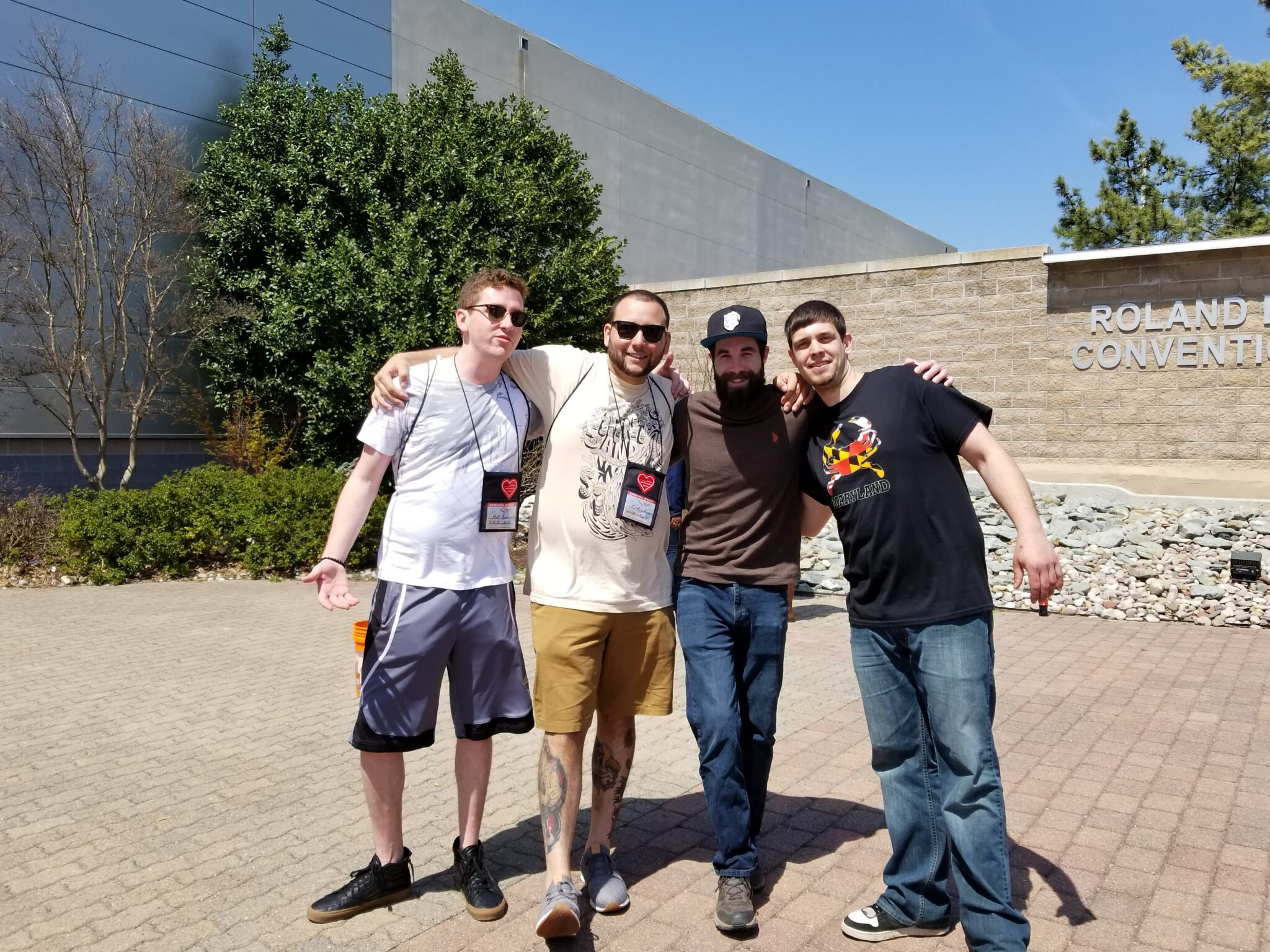 A group of four men smile and pose for a picture with their arms on each other's shoulders pose outside a convention center on a sunny day