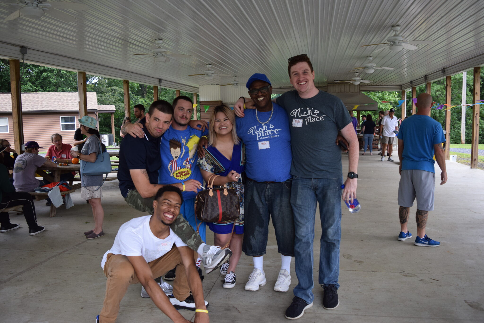 A group of five men and one woman stand together smiling and posing for a picture at an outdoor party under a pavilion