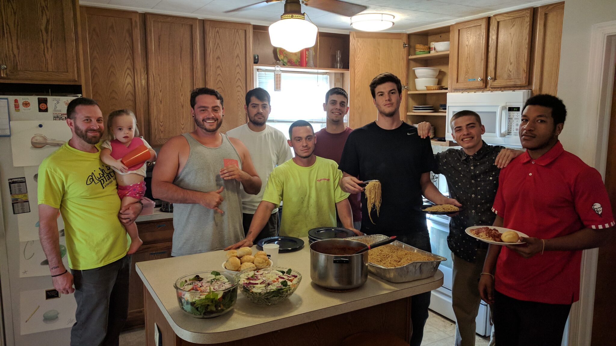 Group of eight men, one holding a toddler, smile and pose for a group photo in a kitchen with wood oak cabinets. They stand around a kitchen island with family size bowls of salad, pasta, sauce, and rolls