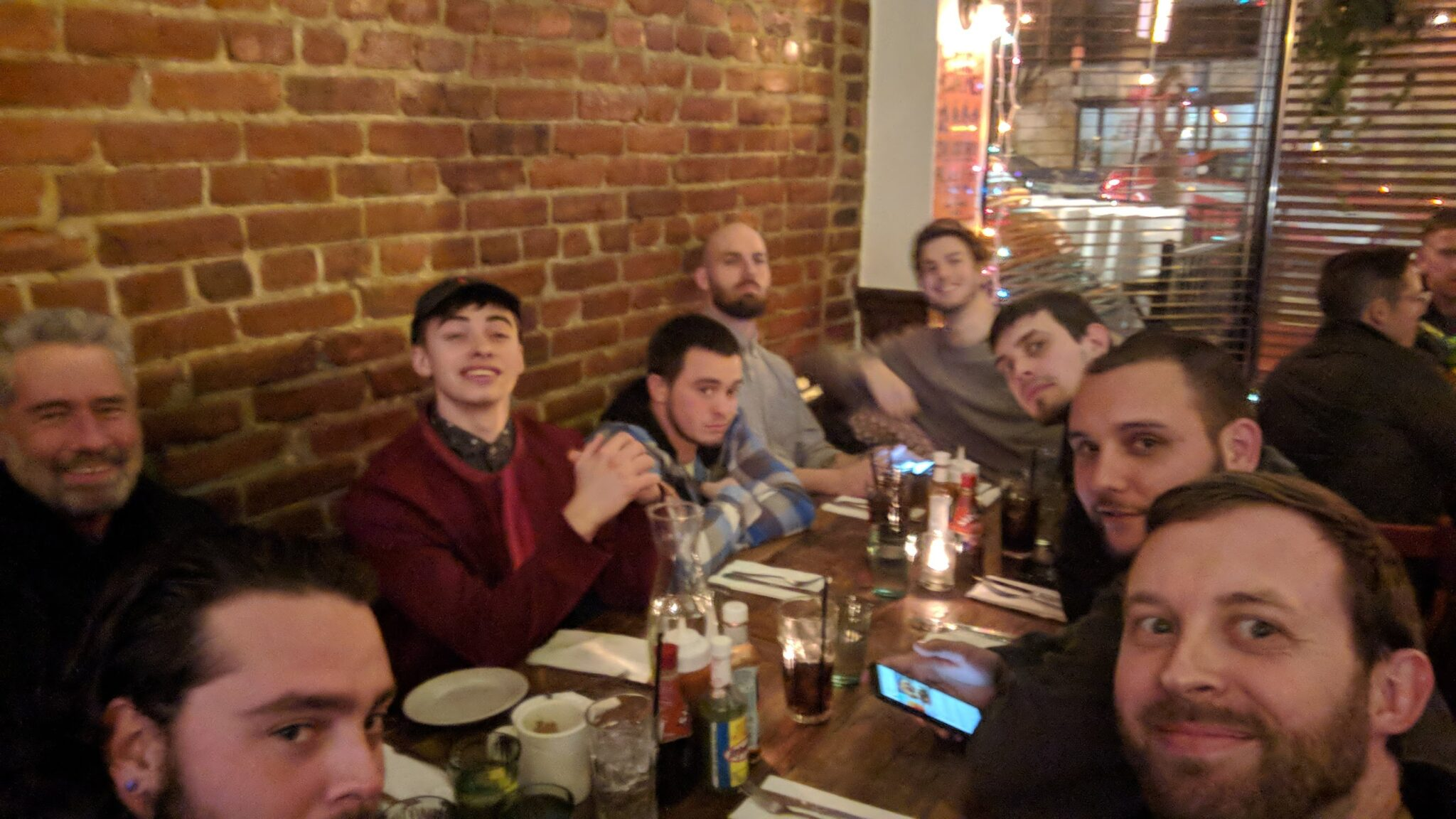 Nine men pose for a group photo seated around a table a restaurant, next to a window and exposed brick wall in the background