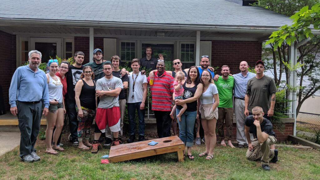 A large group of people of all ages gather for a group photo in a yard outside a home, posing around a lawn game