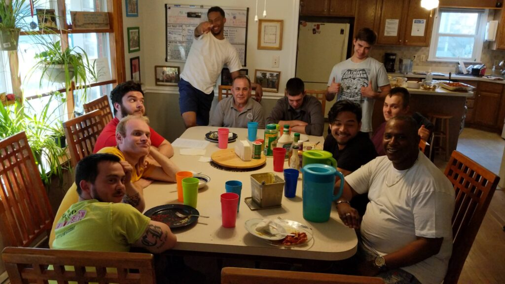 A group of ten men gather around a dining table of a home after sharing a meal, most are seated and smiling and others are standing and posing for the photo