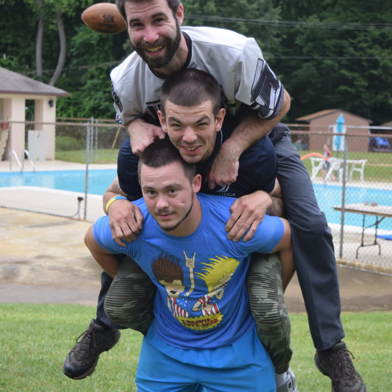 Three men, each one piggybacked on top of the other, pose smiling for a picture in front of a pool