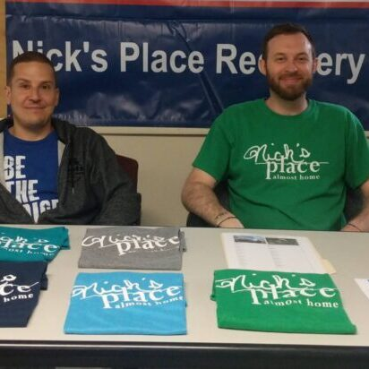 """Two men sit smiling in chairs placed behind at a table with a large """"Nick's Place Recovery Walk"""" banner hangs in the background. The table has t-shirts, flyers, and a signup sheet on it."""